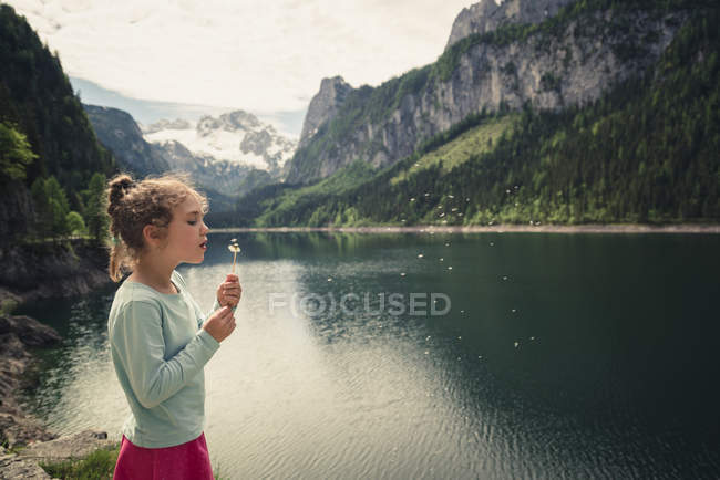 Austria, Gosau, girl with blowball at Gosausee — Stock Photo