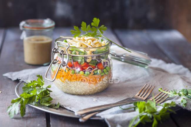 Веселка салат в банку з квіноа, моркву, горох, Червона капуста, солодкий перець, Мен бобові паростки і соусом — стокове фото