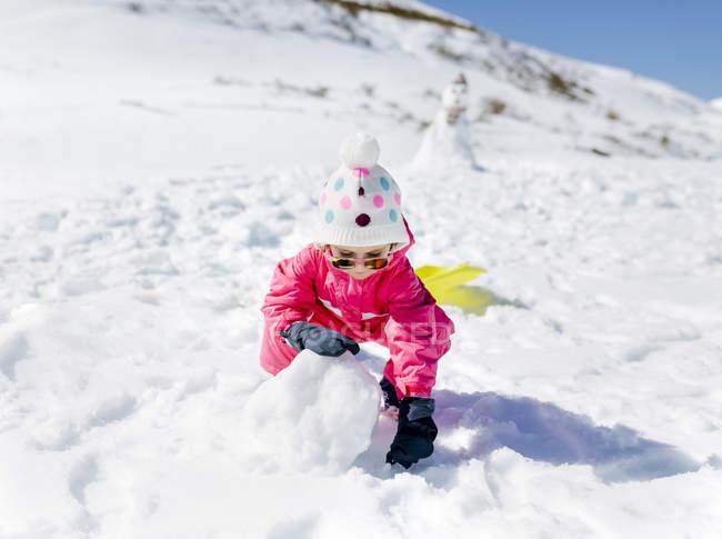 Ragazza caucasica felice che costruiscono pupazzo di neve in inverno — Foto stock