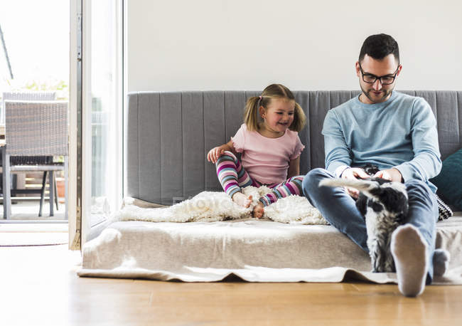 Father and daughter with dog sitting on sofa at home — Stock Photo