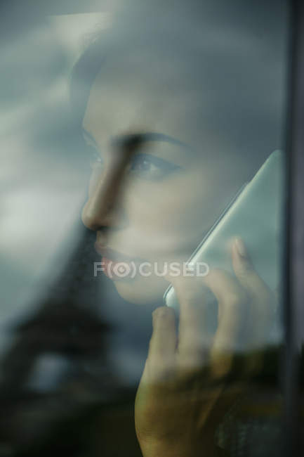 France, Paris, young woman looking through car window while telephoning — Stock Photo