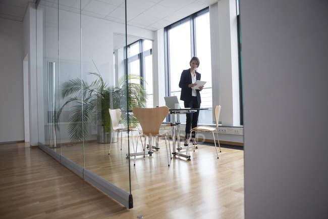 Businesswoman standing in office board room — Stock Photo