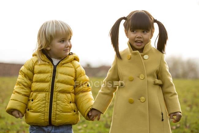 Темноволосая девушка и белокурый мальчик, взявшись за руки Открытый — стоковое фото