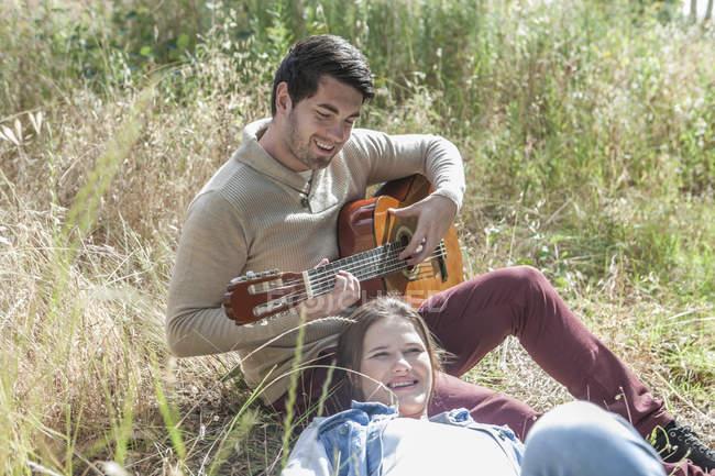 Молодой человек играет на гитаре для своей девушки в поле — стоковое фото