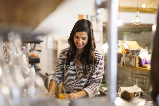 Молода жінка працює її власної маленької кафе — стокове фото