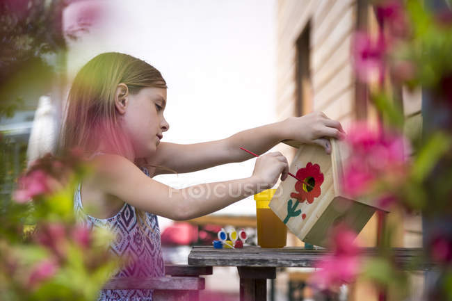 Girl painting red flower on a birdhouse — Stock Photo