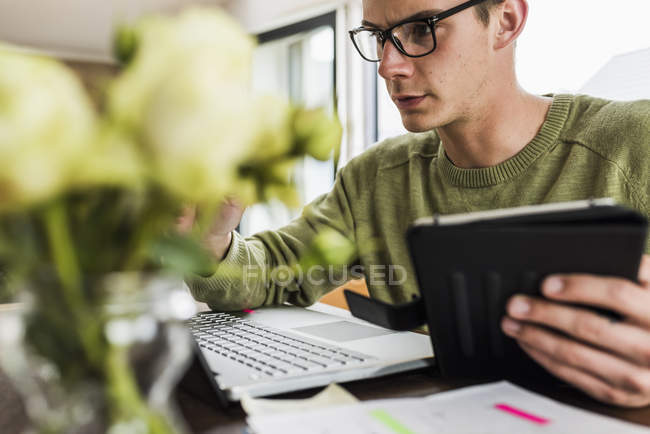 Man at desk with laptop and digital tablet — Stock Photo