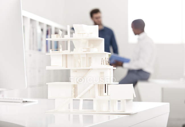 Architectural model on desk in an office with two talking people in the background — Stock Photo