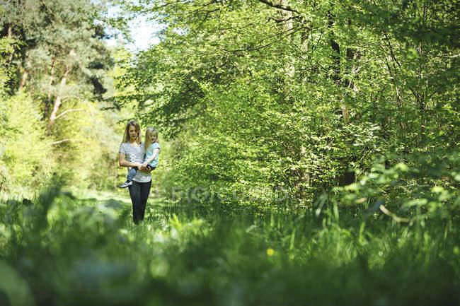 Madre che porta figlia nella foresta — Foto stock