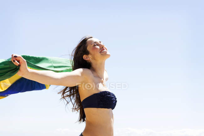 Young brunette woman playing with Brazilian flag at the beach — Stock Photo