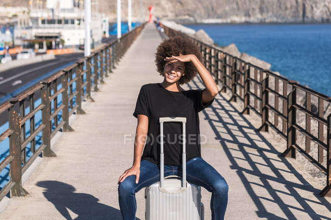 Portrait of smiling woman sitting on her rolling suitcase on a jetty — Stock Photo