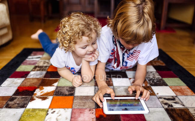 Два мальчика лежат на полу дома, играя с цифровым планшетом — стоковое фото