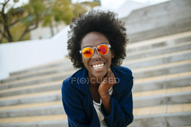 Portrait of happy young woman with nose piercing wearing mirrored sunglasses — Stock Photo