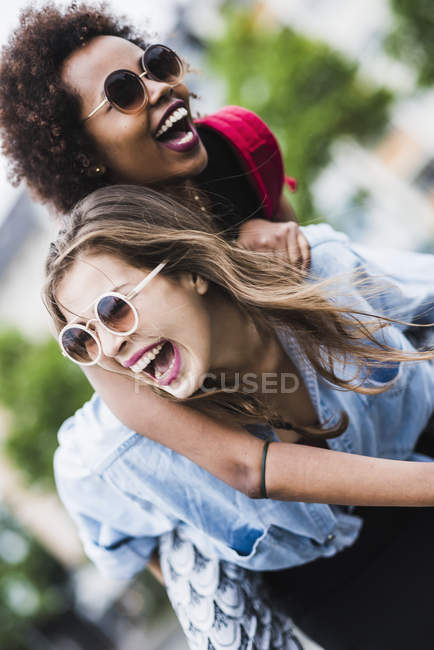 Laughing woman giving her friend a piggyback ride — Stock Photo