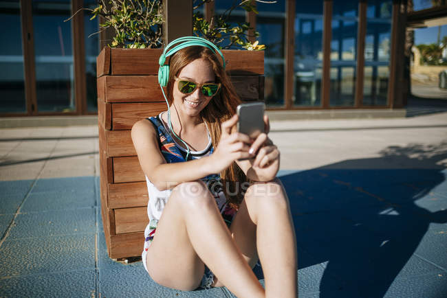 Young woman with headphones and mirrored sunglasses taking selfie with smartphone — Stock Photo