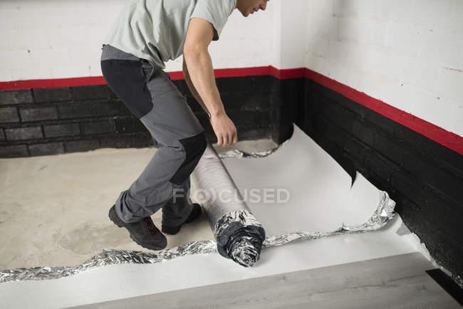 Junger Mann Platzierung ein isolierendes Material für einen Laminatboden — Stockfoto