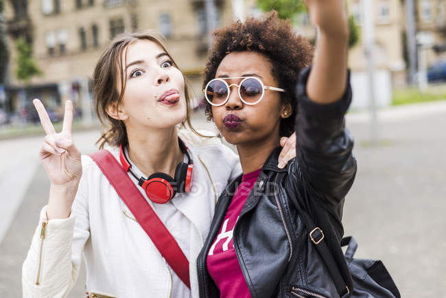 Portrait of two best friends pulling funny faces while taking selfie — Stock Photo