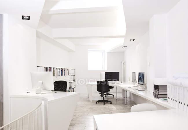 Interior de oficina moderno blanco con computadoras - foto de stock