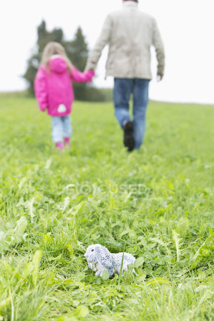 Cuddly toy lying on meadow while man going away with little girl — Stock Photo