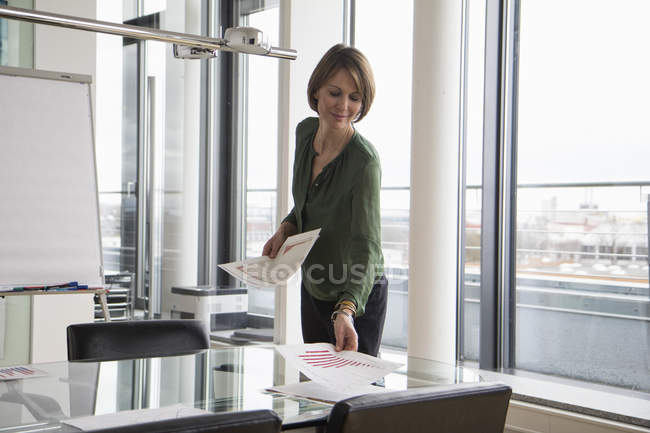 Businesswoman distributing documents in conference room — Stock Photo