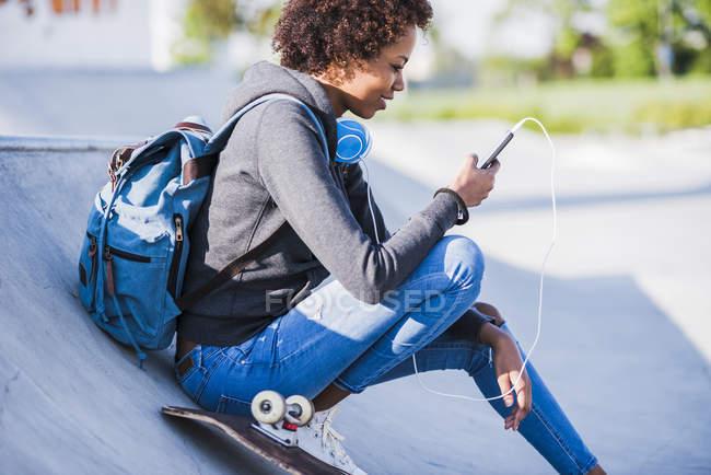 Jovem mulher com fones de ouvido, telefone celular e skate — Fotografia de Stock