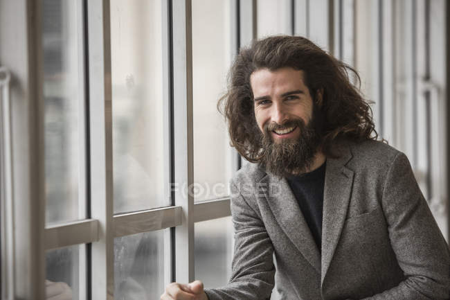 Smiling bearded businessman sitting next to window and looking at camera — Stock Photo