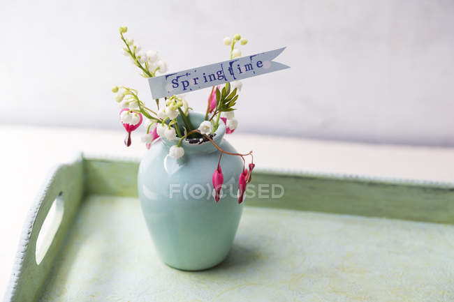 Flower vase of lilies of the valley and lyre-flowers on tray — Stock Photo