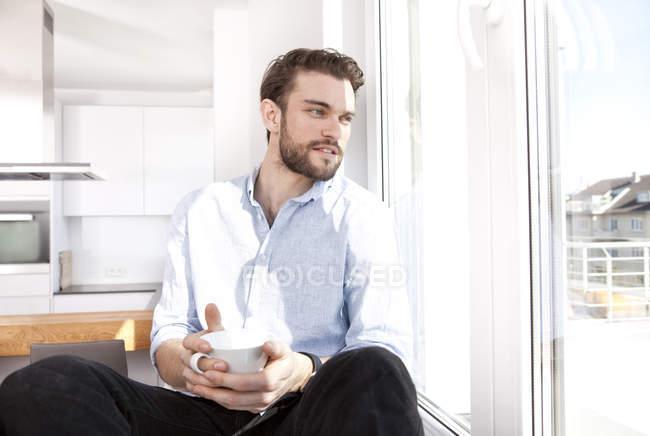 Молодой человек с кофейной чашкой сидит на подоконнике и смотрит в окно — стоковое фото