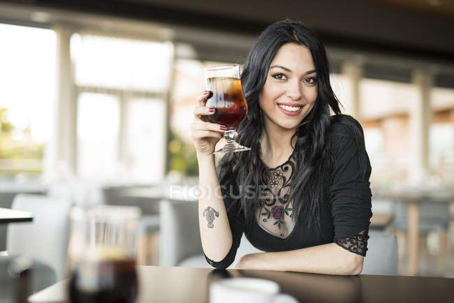 Young woman in cafe drinking cola — Stock Photo