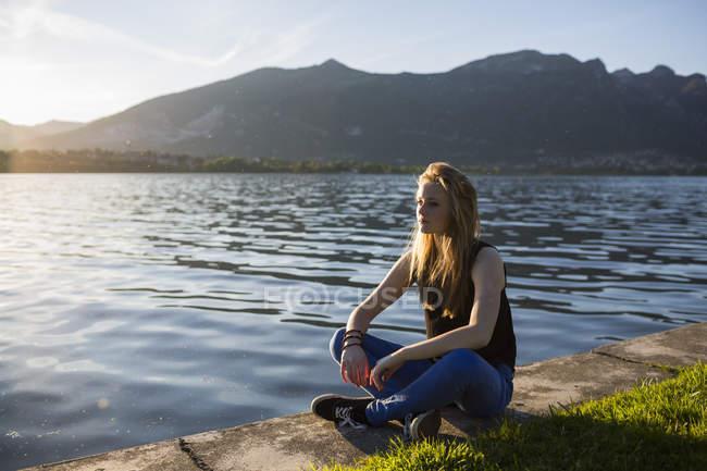 Itália, Lecco, menina adolescente pensativo sentado na beira do lago — Fotografia de Stock