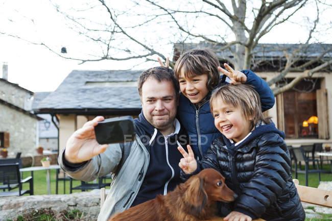 Батько, беручи за selfie з його синів і собака з смартфон — стокове фото