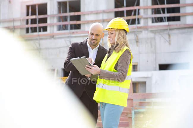 Mulher com chapéu duro e tablet digital conversando com o homem no canteiro de obras — Fotografia de Stock