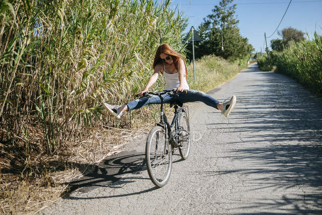 Verspielte junge Frau Reiten Fahrrad auf Feldweg — Stockfoto