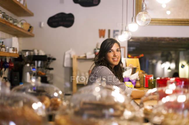 Молодая женщина, работающая в своем маленьком кафе — стоковое фото
