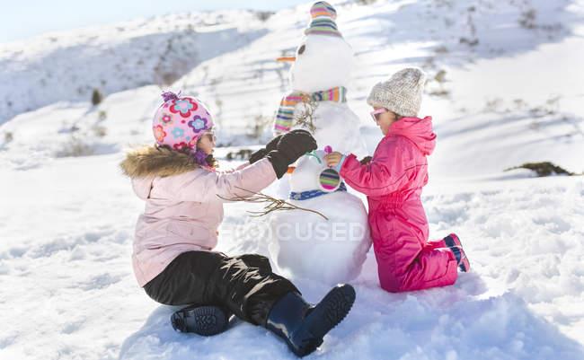 Bambini che giocano con pupazzi di neve in montagne innevate — Foto stock