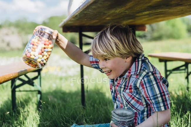 Menino debaixo da mesa segurando vidro — Fotografia de Stock