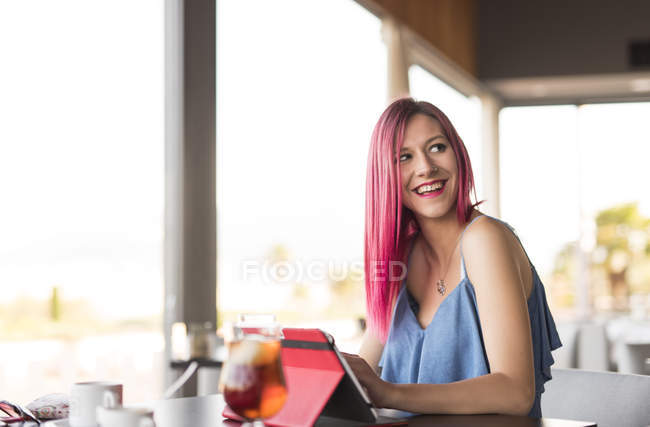 Young woman in cafe using digital tablet — Stock Photo