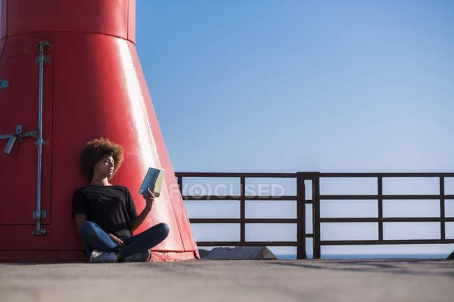 Junge Frau sitzt auf dem Deck ein Buch zu lesen — Stockfoto