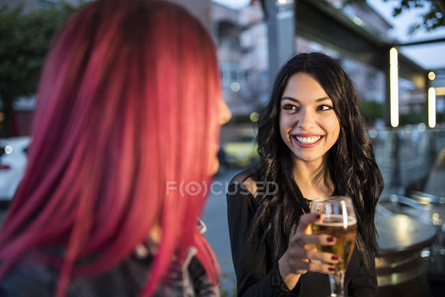 Two female friends sitting in bar and drinking beer — Stock Photo