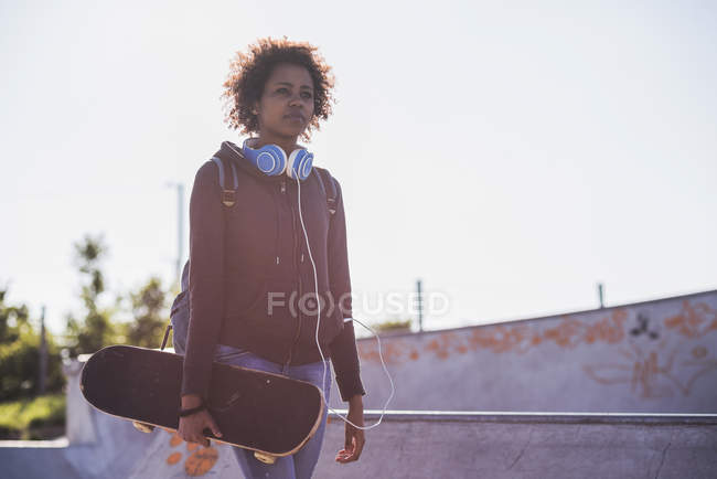 Young woman with skateboard — Stock Photo