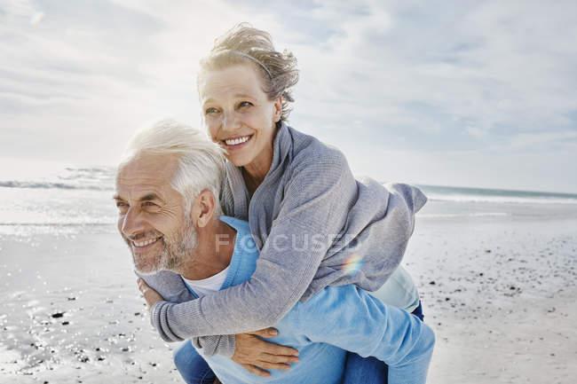 Мужчина катает жену на спине по пляжу — стоковое фото