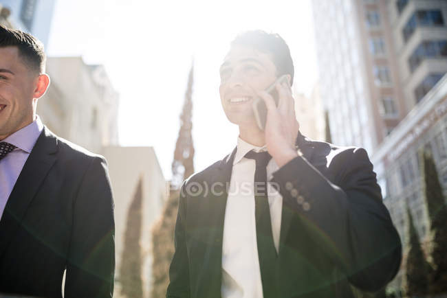 Businessman on cell phone in backlight with colleague — Stock Photo