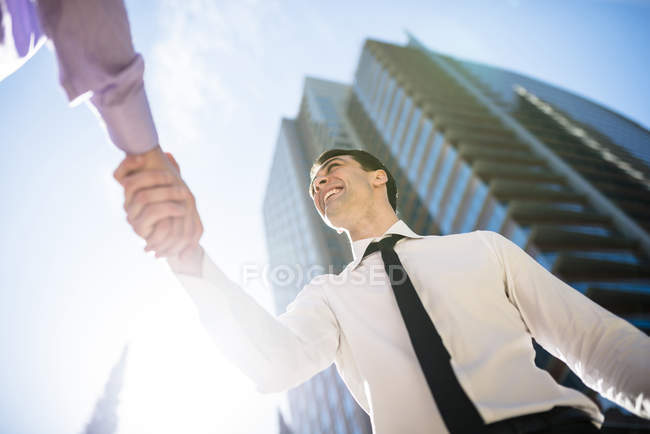 Two businessmen shaking hands in city, bottom view — Stock Photo