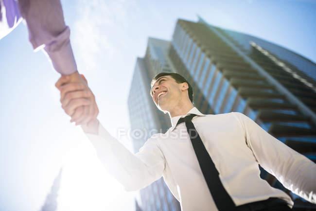 Deux hommes d'affaires serrant la main en ville, vue du bas — Photo de stock