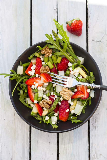 Fresh salad with asparagus, strawberries, rocket, feta cheese and walnuts — Stock Photo