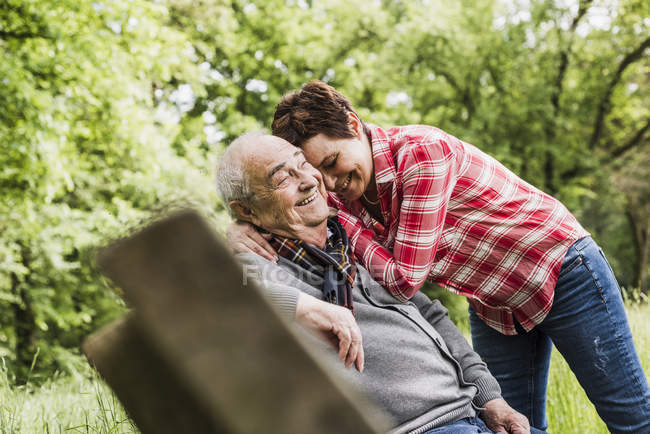 Happy woman hugging her old father sitting on a bench in nature — Stock Photo