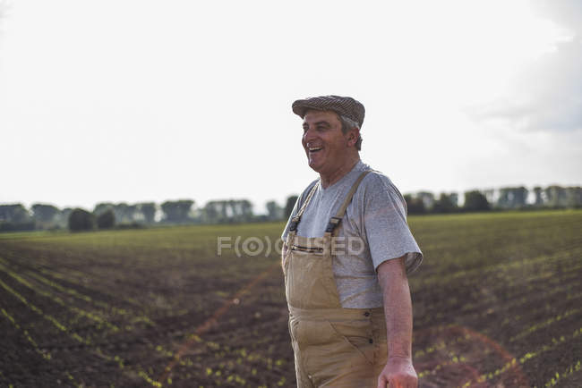 Smiling farmer standing at a field — Stock Photo