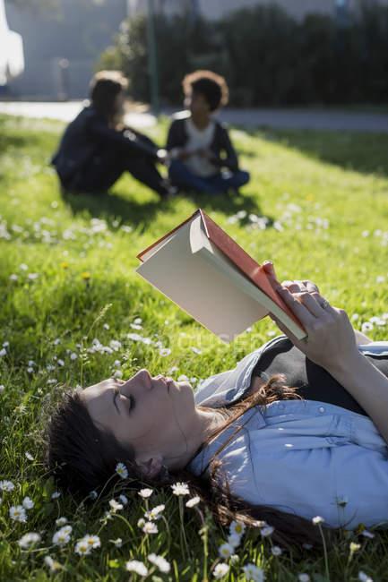 Junge Frau im Park Buch zu lesen — Stockfoto
