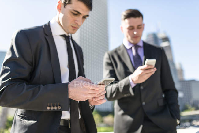 Two businessmen looking at cell phones — Stock Photo