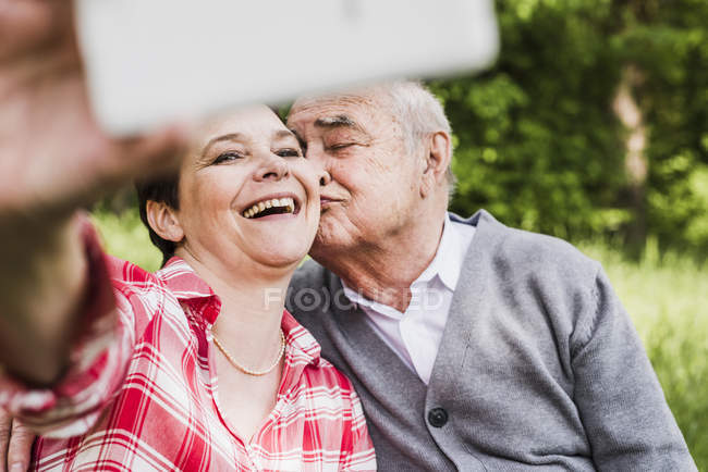 Woman taking selfie with her old father in nature — Stock Photo